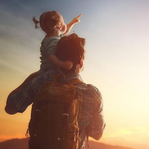 Vater und Tochter schauen Richtung Sonne, Quelle unendlicher sauberer Energie für die Zukunft.