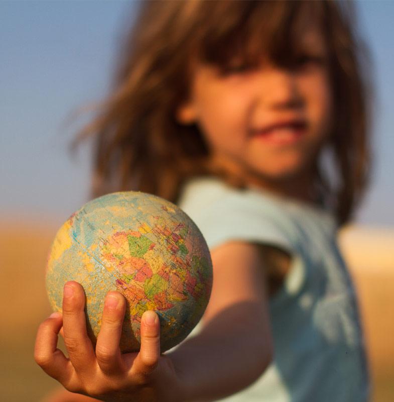 Kind hält eine kleine Kugel der Erde, Symbol für unsere Verantwortung der nächsten Generation einen sauberen Planeten zu überlassen.